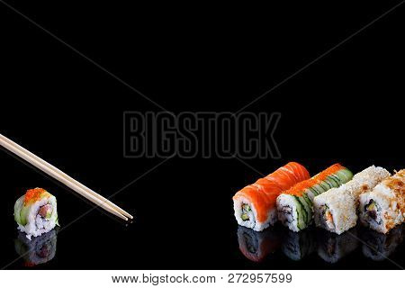 Sushi Set And Chopsticks On Black Background With Copy Space
