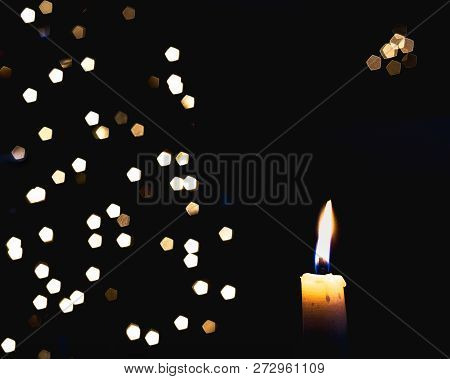 A Candle Flame With Holiday Lights On A Black Background With Space For A Holiday Message.