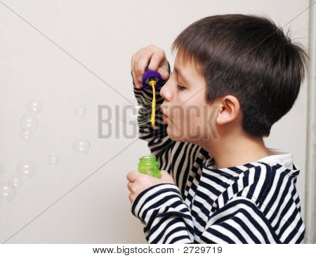 Boy In Striped Vest And A Lot Of Soap Bubbles