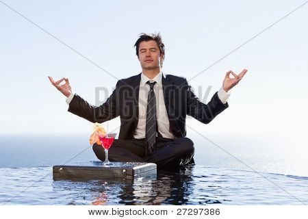 Businessman relaxing in the lotus position with a cocktail in a swimming pool