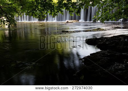 Trees Leaning Over A River With A Waterfall In The Background.  Old Stone Fort State Archaeological