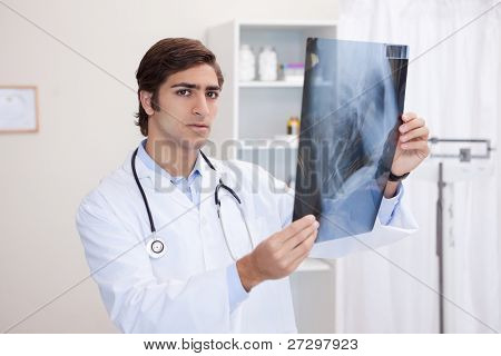 Young male doctor analyzing x-ray
