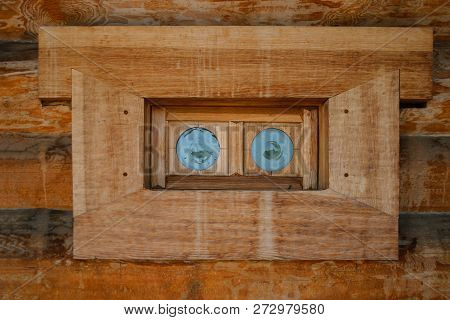 An Old Wooden Window With Small Round Colored Glasses In A Wooden House Of Logs. Traditional Wooden