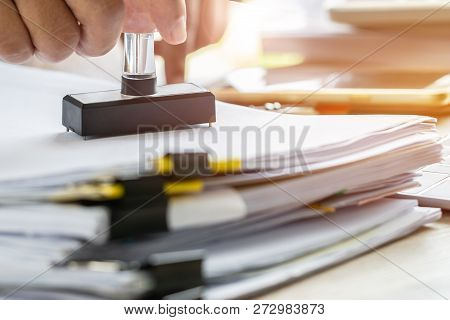 Business Person's Hand Stamping On Approved Application Form Or Notary Public In Office Stamping Doc