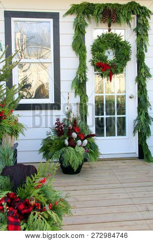 Front door and porch decorated with Christmas wreath, ribbons and floral arrangements.