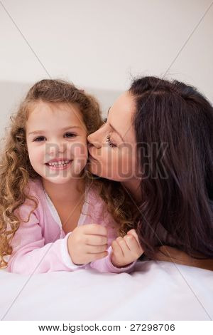 Young mother giving her little daughter a kiss