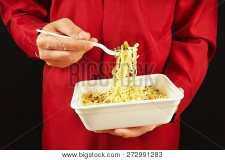 Hands Of Man In A Red Shirt With Container With Cheap Instant Noodles On A Black Background