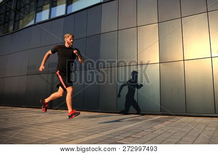 Sporty Young Man Running Outdoors To Stay Healthy, At Sunset Or Sunrise. Runner.