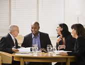A group of business people are in a meeting in an office.  They are talking and laughing and looking away from the camera.  Horizontally framed shot. poster