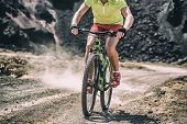 Mountain bike MTB biking athlete man in mountains landscape jumping riding bicycle. Professional bicycle rider body crop training outdoors. Sport and fitness background. poster