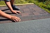 Roofer hands laying Asphalt Shingles on house construction roof. Roofing construction with Asphalt Shingles. poster