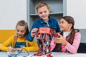 smiling schoolchildren making electric robot in stem class poster