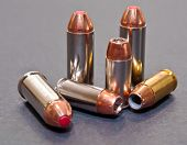 Six bullets, three 40 caliber hollow point and three 44spl on a gray background poster