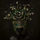 Head Medusa, creature of Greek mythology. pieces made by hand with goldsmiths and metals such as gold and copper. wears a helmet of green and gold snakes poster