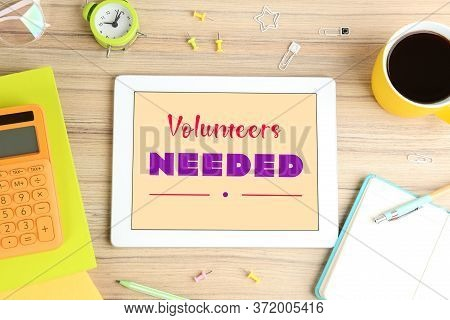 Modern Tablet With Text Volunteers Needed On Wooden Table, Flat Lay