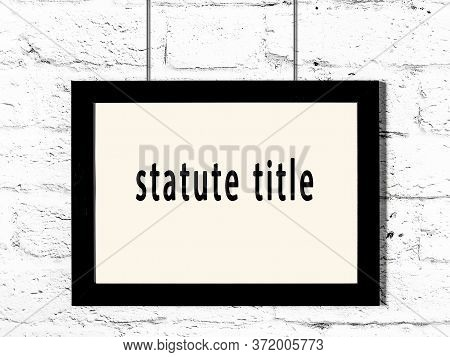Black Wooden Frame With Inscription Statute Title Hanging On White Brick Wall