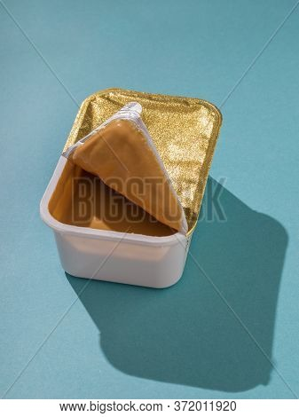 Open Plastic Container With Peanut Paste On A Blue Background. Natural Peanut Cream.