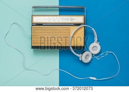 Retro Radio And White Headphones On A Two-tone Background. Radio Broadcast Live. Vintage Technique.