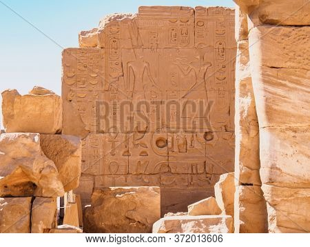 Egyptian Legends Painted On Ruined Brickwall, Medium View. Ancient Ruins Of Karnak Temple. Photograp