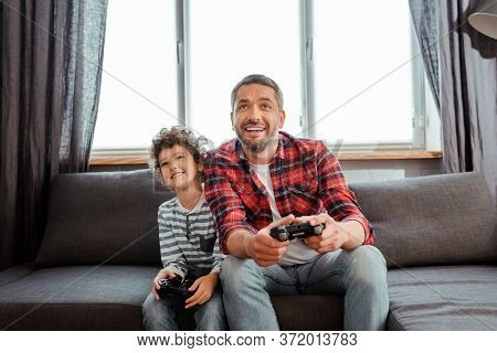 Kyiv, Ukraine - May 14, 2020: Handsome Father And Happy Son Playing Video Game In Living Room