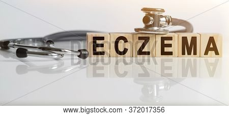 Eczema The Word On Wooden Cubes, Cubes Stand On A Reflective White Surface, On Cubes - A Stethoscope