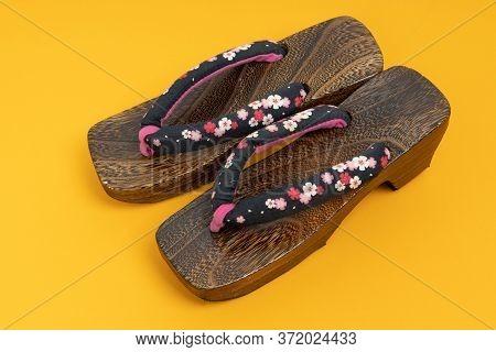 Japanese Traditional Geta Sandal On Yellow Floor. Traditional Japanese Asian Wood Footwear Called Ge