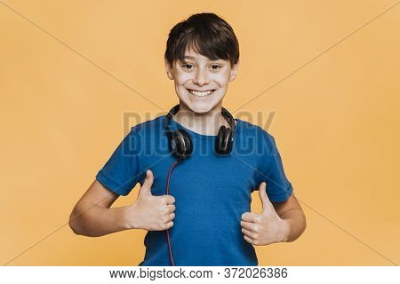 Grateful Young Teenager With Headphones On His Neck, Dressed In Blue T-shirt, Smiling Widely, Shows