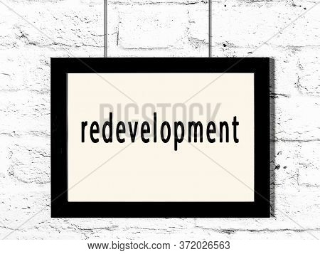 Black Wooden Frame With Inscription Redevelopment Hanging On White Brick Wall