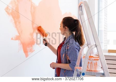 Beautiful Woman Painting Wall In Her New Apartment. Renovation And Redecoration Concept.
