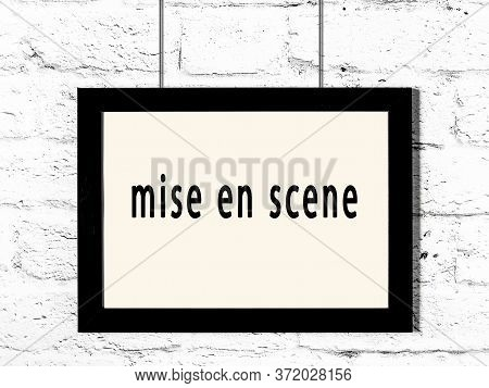 Black Wooden Frame With Inscription Mise En Scene Hanging On White Brick Wall