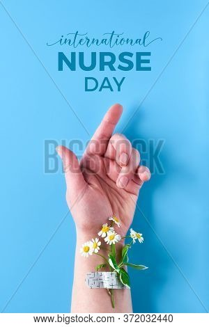 International Nurse Day. Hand Of Mature Woman With Chamomile Flower Bouquet Attached With Medical Ai