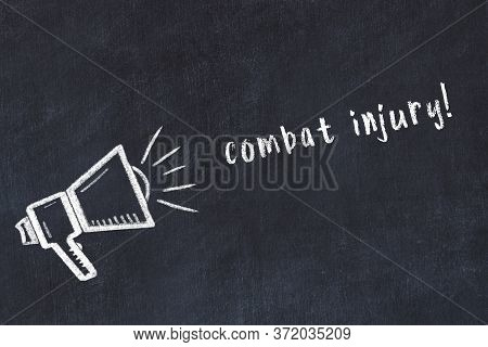 Chalk Drawing Of Loudspeaker And Handwritten Inscription Combat Injury On Black Desk