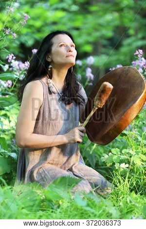 Shamanic Woman Playing On Shaman Frame Drum At Dawn In The Forest On Background With Leaves And Flow