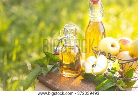 Two Glass Bottles Of Apple Cider Vinegar And Fresh Ripe Apples On A Wooden Nature Background. Copy S