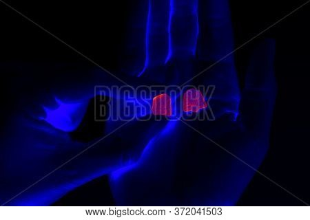 Taking Ecstasy Pills In Club Under Black Light. Rolling At Party.