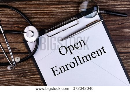 Open Enrollment Text Written In A Notebook Lying On A Desk And A Stethoscope. Medical Concept.