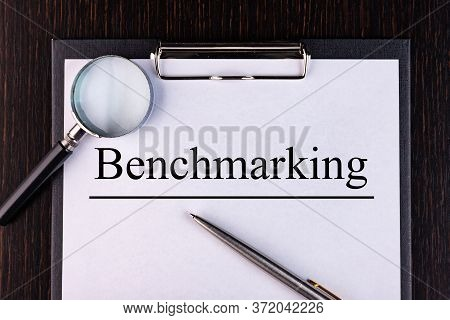 Text Benchmarking Is Written On A Notebook With A Pen And A Magnifying Glass Lying On The Table. Bus