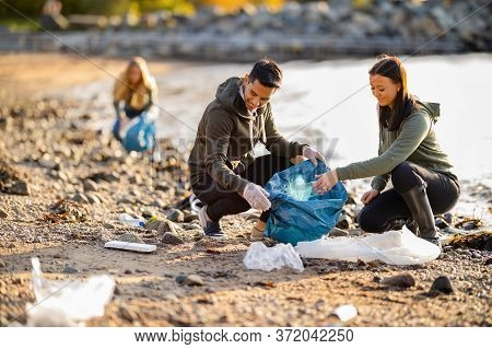 Team Of Dedicated And Smiling Volunteers Collecting Garbage At Beach