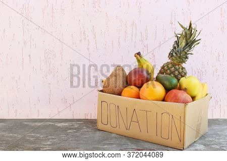 Donation Box With Food On Old Wooden Background.