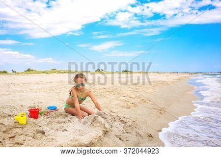 Child Plays  With Sand On The Beach.
