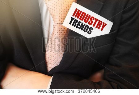 Businessman Holding A Card With Text Industry Trends. Business Concept