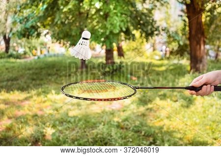 Racket With A Shuttlecock In The Air On A Background Of Greenery. Playing Badminton In The Open Air