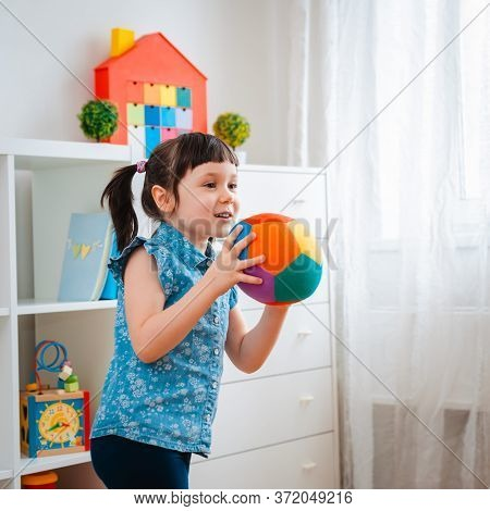 Children Little Girl Play In A Childrens Game Room, Throwing Ball. Concept Of Interaction Parent And