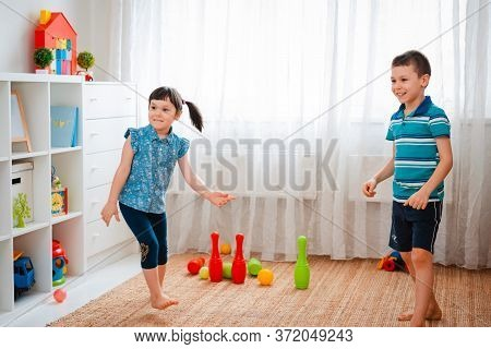 Native Children Boy And A Girl Play In A Childrens Game Room, Throwing Ball. Concept Of Interaction