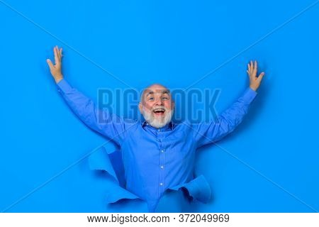 Bearded Man Looking Through Hole In Paper. Excited Bearded Man Making Hole In Paper. Man Looking Thr