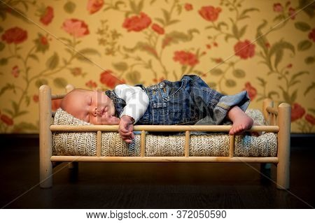 Babe In Denim Overalls Sleeps In A Little Cot Toy. Care For Newborn Children.