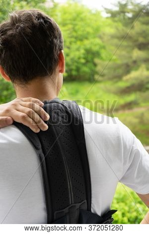The Teen In The Corrector For The Spine On A Green Natural Background. Back Support For Muscle Back