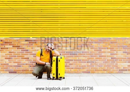 Man In An Orange Shirt Waiting On The Floor In The Street With A Suitcase