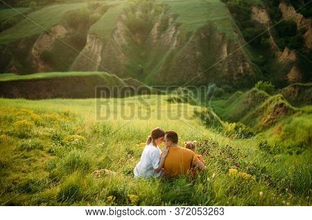 Family With Little Daughter Rests While Walking In The Meadow On Ravine Background. Back View.