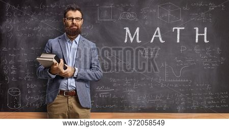 Math teacher holding books and pointing at a blackboard with formulas